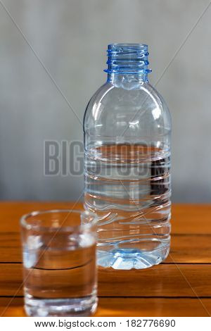 Drinking water in glass and plastic bottles on a wooden table.