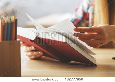 Close up of female hands flipping book pages at workplace