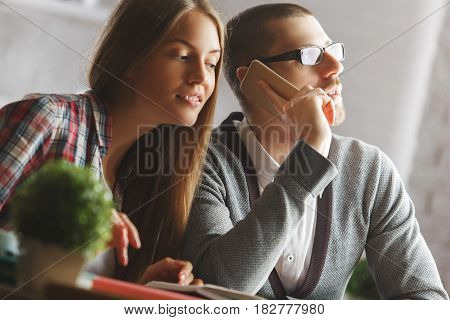 Attractive european male and female talking on the phone in modern office. Communication concept