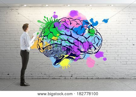 Businessman in brick interior looking at colorful human brain drawn on wall. Creative mind concept. 3D Rendering