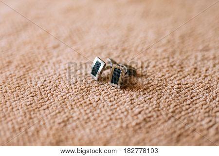 Men's cufflinks for a shirt on a fabric texture.