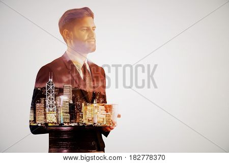 Handsome thoughtful young businessman drinking coffee on abstract night city background. Employment concept. Double exposure