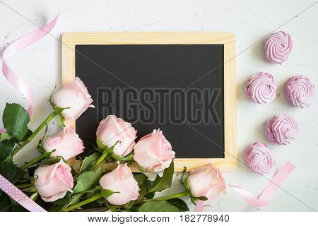 Pink rose and pink dessert around chalkboard at white table. Top view copy space. Mothers day background.