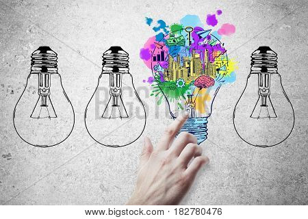 Hand pointing at abstract drawn lamps and business sketch on concrete background. Idea concept