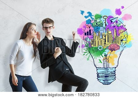 Attractive successful young caucasian man and woman on concrete background with colorful sketch. Business ideas concept