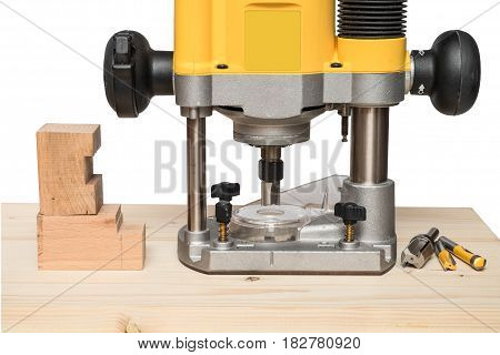 Yellow plunge router, cutters and milled board on wooden table. Isolated on white background.