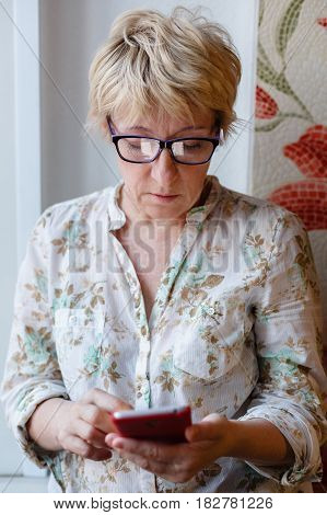 Front view of mature woman in glasses standing and using device.