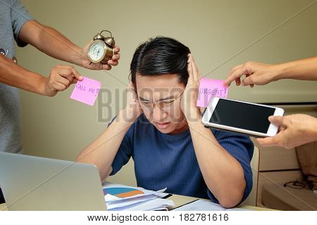 Stressed young business man sitting at table Busy day of an employee concept