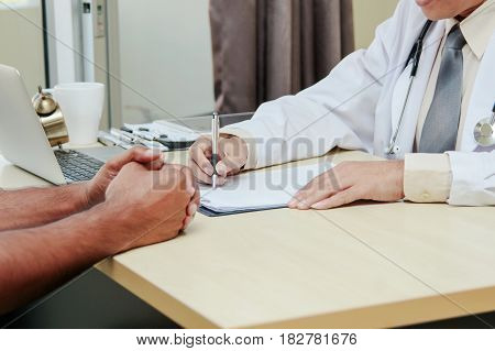 Asian Doctor Talking And Taking Notes With Male Patient (consultation)