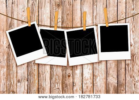 Photos on rope with clothespins on wooden background