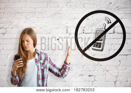 European girl on white brick background using cellphone despite the inhibitory sign. Addiction concept