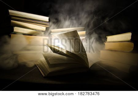 Many Old Books In A Stack. Knoledge Concept. Books On A Dark Background With Smoke Elements. Bewitch