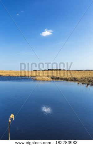 Early evening at a quiet and calm lake and sky reflections in summertime
