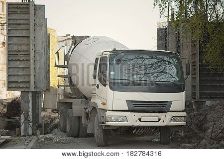 Cement mixer truck parked in front of a new building under construction with scaffolding.