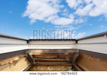Installing Skylight (roof window) in New Modern Passive Wooden House against blue sky