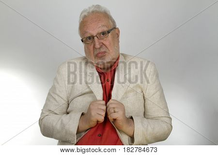 Bearded senior with glasses twitches at his jacket - on bright background