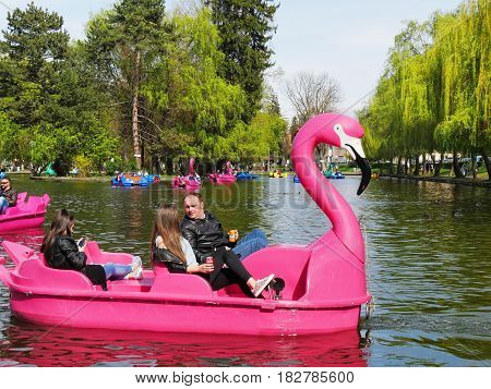 CLUJ-NAPOCA ROMANIA - APRIL 17 2017: Families spend quality time on pleasure boats on the lake in central park. People pedal swan boats and dragon pedal boats.