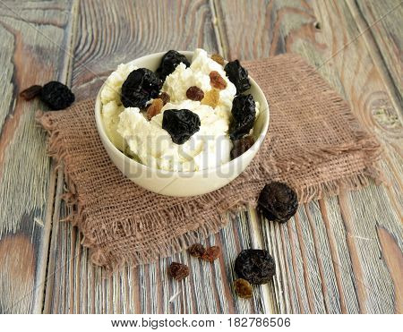 Cottage cheese is classical dairy product. Cottage cheese prunes raisin are in a drinking bowl.