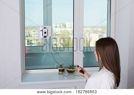 Woman Cleaning Windows With Robotic Cleaner