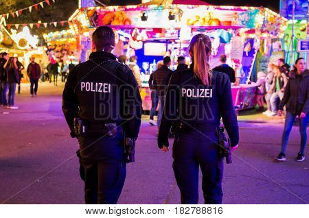 Frankfurt am Main, Germany - April 19, 2017: Police officers walking in dippemess in Frankfurt am Main, Germany at night.