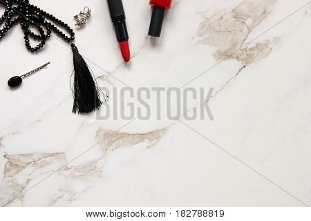 Red and black fashion and beauty supplies frame white marble copy space.