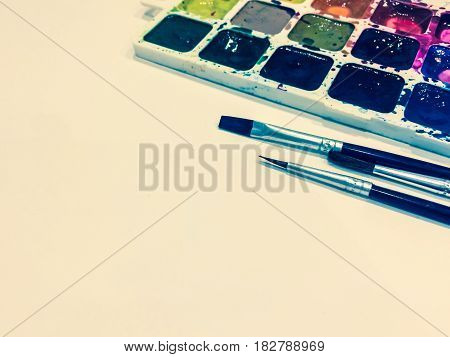 Mockup with a Blank Page, Paints and Brushes with Place for Your Text. Toned Studio Photo