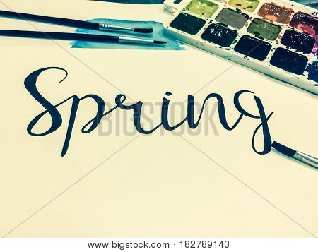 Mockup with a White Page, Word Spring, Paints and Brushes. Toned Studio Photo
