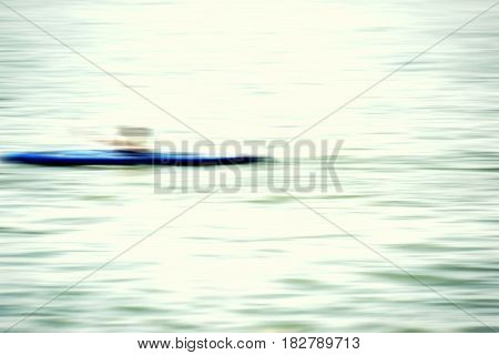 The blurred and abstract outlines of a canoe on a river.