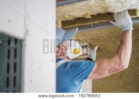 House Insulating by Caucasian Worker. Home Roof Remodeling.