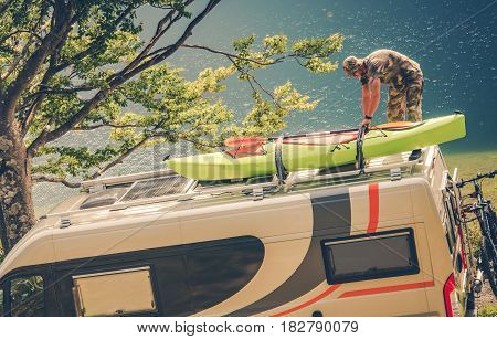 Men Installing Kayak on the RV Camper Van. Preparing For the Next Motorhome Trip.