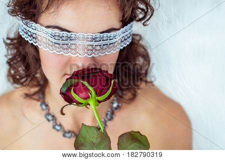 Close up portrait of a beautiful woman with clear white bandage on eyes that holding and smells red rose flower