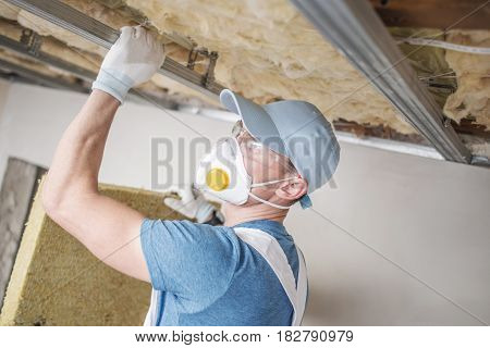 Wool Home Insulating. Caucasian Home Renovation Worker with Mineral Wool.