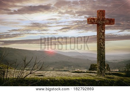 Stone cross with a stunning sky at sunset