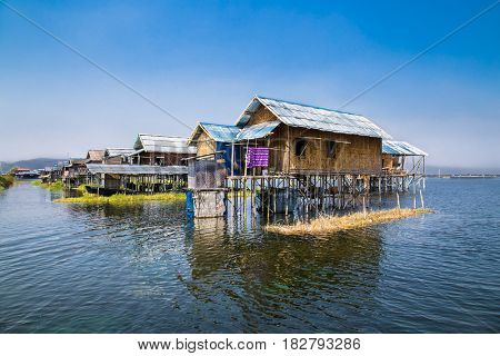 Ancient houses and their reflection in the water on the Inle Lake, Myanmar. (Burma)