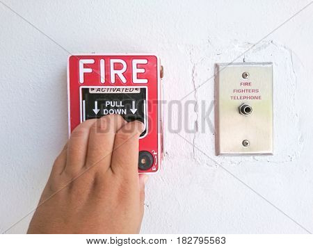 Hand pulling down the fire alarm button