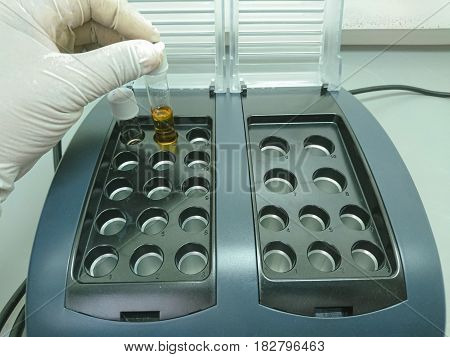 Scientist placing a test tube in a heat block Chemical oxygen demand Waste water analysis.