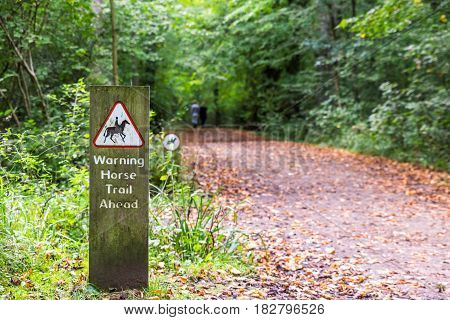 Warning Horse Trail Ahead sign in english forest park.