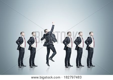 Row of businessmen candidates for a good vacancy is standing against a gray background. Oned of them is jumping.