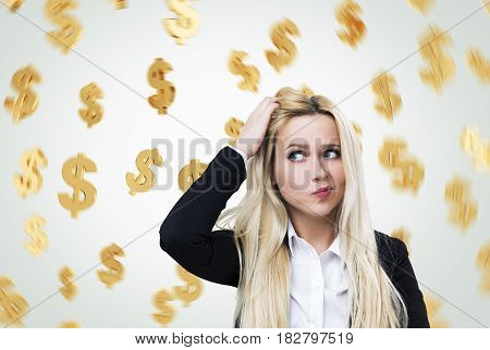 Portrait of a confused blond businesswoman scratching her head while staning near a gray wall with dollar signs