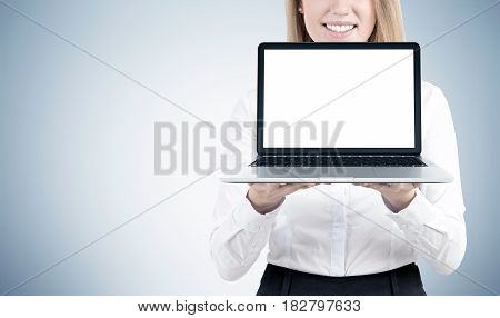 Close up of a blond businesswoman holding a laptop with a blank screen and standing near a gray wall. Mock up