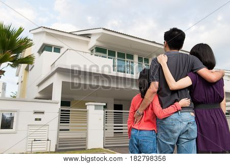 Parents and kid standing in front of dream house in modern residential houses