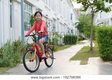 Little Asian girl cycling at bike trail of modern residential area