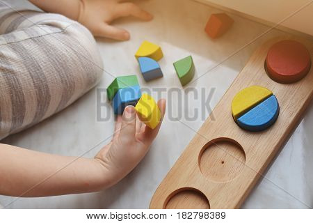 The boy arranges geometric wooden figures. Developing games for the child. Concept education.