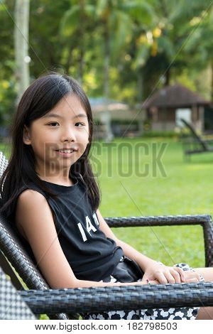 Portrait of little Asian girl sitting on deck chair outdoor