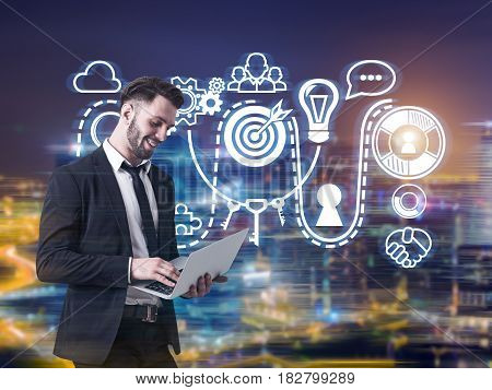 Portrait of a young bearded businessman standing with his laptop against a night city panorama with a buisness idea sketch in the air.