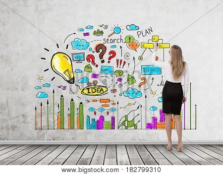 Rear view of a blond businesswoman drawing a bright business idea sketch on a concrete wall in a room with wooden floor.