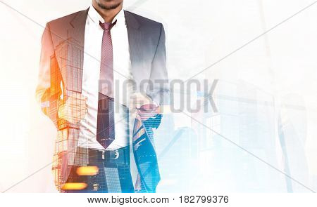 Close up of an African American businessman wearing a suit and a red tie and standing against a large glass skyscraper. Mock up toned image double exposure