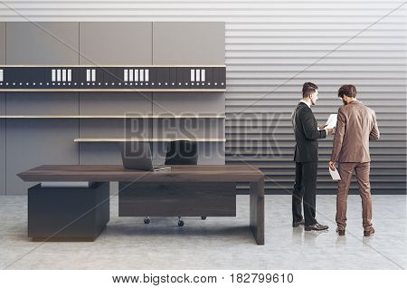 Business people in an interior of a clerk office with a gray perforated wall a large desk and a bookcase with folders standing on them. 3d rendering toned image