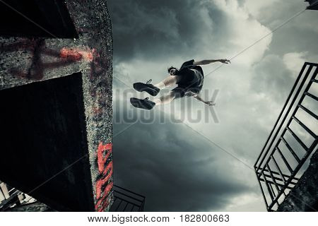 young man doing parkour jump in the city shot 