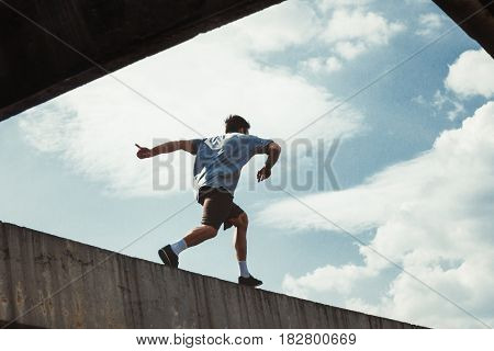 young man doing parkour in urban space in the city  sunny spring summer day